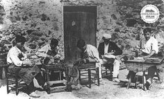 Alpargateros at work, some making the sole, others sowing the canvas. Early 20th century
