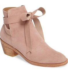 Ballet-inspired ankle ties wrap around the split shaft of a chic almond-toe bootie elevated by a tapered stacked heel.