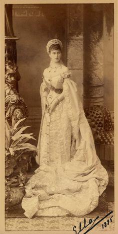 """Grã-duquesa Elisabeth Feodorovna. Ela está em pé com a cabeça voltada ligeiramente para a direita, segurando um leque. Ela está usando um vestido da corte imperial, incluindo um longo comboio reunidos em frente a ela, uma faixa e uma tiara. Há uma série de itens de mobiliário em torno dela e um pano de fundo pintado por trás. A fotografia é assinada e datada """"Ella 1885 'no canto inferior direito."""