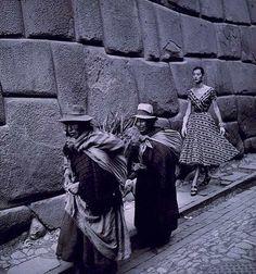 Fashion model following women down a street in Peru, 1950