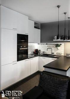 Biała kuchnia, wydzielona z części salonu. Fronty w połysku dodają lekkości, dlatego kuchnia nie dominuje we wnętrzu. Szara ściana stanowi doskonałe tło do bieli frontów i kafelkó ...