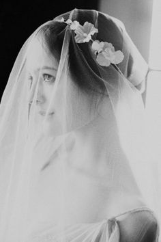 "Interesting. Put the veil under the bottom of the flower ""crown"" and then flip it over your face....then take it off after the ceremony..."