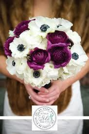 The bridal bouquet will be a clutch of ivory ranunculus, ivory spray roses, dark purple ranunculus, white anemones, and white cymbidium orchid blooms with pink centers wrapped in ivory ribbon with a crystal broach accent.
