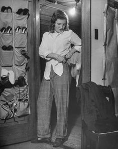 A young lady borrowing clothes from her (I'm guessing) brother - love the shoe holder on the door, one doesn't see those too often in vintage photographs.