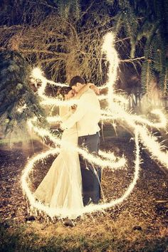 Amazing effects! It's like a fairy tale scene.... Its a long exposure shot bride and groom stand still whilst some one ran around them with a sparkler!