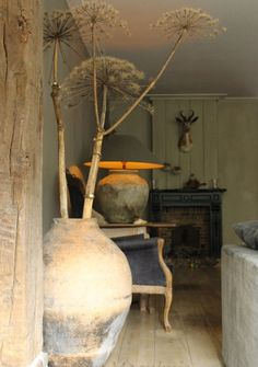 What a perfectly wonderful room...Unusual branches in the rough hewn pot make for terrific interest and balance.