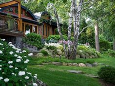 A big birch tree shades this backyard in the afternoon. The yard slopes down significantly as it reaches lake's edge, so a rock garden with larger and then smaller boulders makes that transition feel more natural.