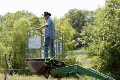 Using an IBC cage strapped to a tractor to make a cherry-picker for hop harvest... Photo from Oast House Hops