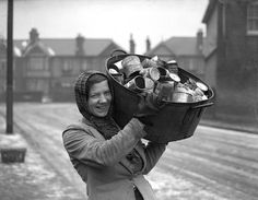 A female dustman carries a tub full of old cans back to her dustcart. Women in Ilford have become the first to work as dustwomen during the war.