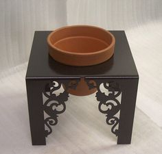 "This flower pot stand is handmade and designed by Knob Creek Metal Arts. This planter is made from solid steel and features beautiful scroll cuts. Dimensions are approx 10 1/2"" t x 10 1/2"" w x 10 1/2"" l. Comes complete with a 6 3/4"" clay pot. ..... by knobcreekmetalarts"