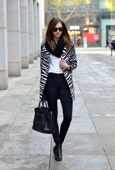 Comprar ropa de este look:  https://lookastic.es/moda-mujer/looks/abrigo-camiseta-con-cuello-barco-vaqueros-pitillo-botines-chelsea-bolsa-tote-bufanda/1106  — Abrigo de Rayas Horizontales Blanco y Negro  — Camiseta con Cuello Barco Blanca  — Vaqueros Pitillo Negros  — Bufanda Negra  — Bolsa Tote de Cuero Negra  — Botines Chelsea Negros
