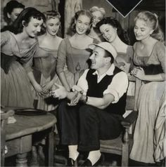 """Gene Kelly surrounded by lovely lasses on the set of """"Brigadoon"""" in 1954"""