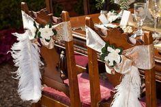 Idée DIY pour un mariage sur le thème Gatsby : quelques plumes d'autruches joliment attachées aux chaises des invités.