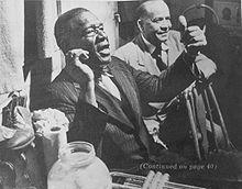 Papa Celestín (Napoleonville, de Luisiana, el 1 de enero de 1884 - Nueva Orleans, 15 de diciembre de 1954) fue un trompetista y cantante norteamericano de jazz tradicional.  Famoso por la manera en que se adueñaba del escenario durante sus interpretaciones, fue uno de los pioneros de la música jazz, en los tiempos en que era tan reciente que aún no la llamaban ' jazz '    Imagen: Con el clarinetista Alphonse Picou (al fondo). Foto de Stanley Kubrick. 1950.