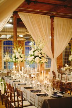 Beautiful white, grey and blue wedding in a rustic space. The white curtains and the tall centerpieces make this so romantic.