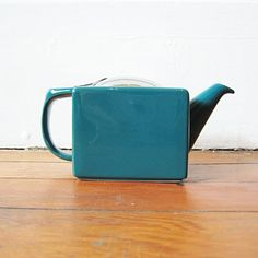 "SMALL KABUKI TEAPOT  This small teapot has a cubical, deco shape. It is made of sturdy ceramic, with a removable stainless steel infuser and lid. It holds 16 oz. of liquid in a neat and petite container, perfect for the office. 4"" high and 6 1/2"" from handle to spout.  Designer:  Beehouse, Japan  Dimensions: 3 3/4"" square body, holds 16 oz  1 color teal  www.raredevice.net"