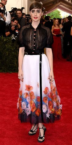 The Most Jaw-Dropping Dresses at the 2015 Met Gala | LILY COLLINS | in a Chanel Haute Couture black bolero top with full skirt featuring watercolored flowers and T-strap pumps, plus Chanel Fine Jewelry.