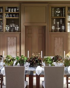 At the dining end of the Brown Room, Martha gathers assorted fancy-leafed begonias to give each of her guests a different perspective on the growing centerpiece. Open shelves present some of Martha's collection of antique glassware, mainly American but interspersed with European examples. The walls were painted using a faux-bois technique and the table, custom-designed by Martha, features a thick, richly-veined marble top.