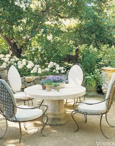 Beautiful stone table & cream & iron chairs in shaded garden. Ginny Magher in Provence garden inspiration outdoor living