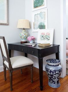 A mix of feminine porcelain pieces and atmospheric watercolors pairs beautifully with a handsome desk and side chair.