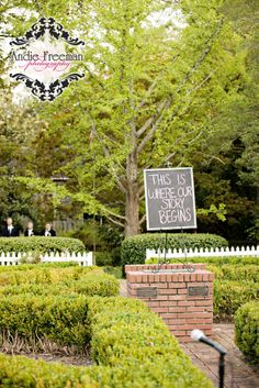 """Garden wedding ceremony site with white arbor, pink azaleas, and tiffany blue bows. Sign reads, """"Our story begins here."""" Industrial Fall Wedding. Photography: Andie Freeman Photography, www.TheAthensWedd... Venue: The Brickyard, Colbert, GA Make-up:  Bombshell Creations www.BombshellCreations.com"""