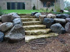Steps in boulder retaining wall Concrete Deck, Stamped Concrete, Rock Wall Gardens, Boulder Retaining Wall, Patio Wall, Garden Yard Ideas, Outdoor Spaces, Outdoor Decor, Patio Design
