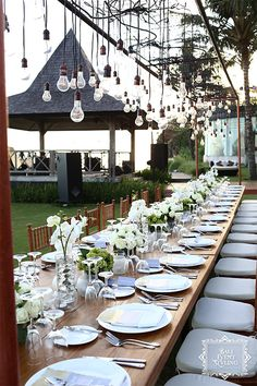 Dinner set-up at a Bali beach wedding with hanging lightbulbs for a rustic-yet-romantic touch, and and array of white flowers and green hydrangeas on a wooden table. Styling by http://balieventstyling.com