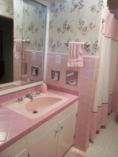 This Vintage Bathroom has the classic wallpaper,pink tile and yet, double sinks! This must be a late 1950's bathroom.