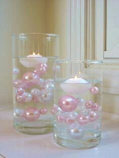 Floating candles in vase with water and pearls in different sizes