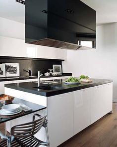 SINTONÍA EN BLANCO Y NEGRO La cocina, con mobiliario procedente de Gibo, combina los frentes en acabado blanco alto brillo, y encimeras de Silestone negro, el mismo color que panela la gran campana de isla.