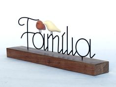 Escultura em arame com passarinhos de cerâmica em base de madeira. Essa madeira pode variar de tamanho e tonalidade de acordo com a disponibilidade