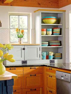 Easily add personality to your kitchen with colorful dishware and collectibles on display in open cabinetry. The mix of yellow, orange, and blue brightens this charming country kitchen and allows practical elements to provide a starting point the room's color palette.