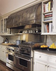 The 60-inch BlueStar RNB Heritage Classic range has six burners, two extra-large ovens, and a professional-style raised griddle and infrared broiler. The metal hood is custom-made with an antique pewter finish.