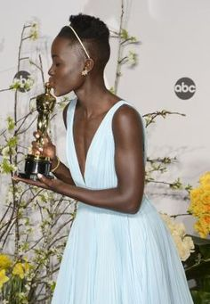 """2014: The Year in Entertainment - Photos - UPI.com Lupita Nyong'o, winner of best supporting actress for """"12 Years A Slave"""" kisses her Oscar backstage during the 86th Academy Awards at the Hollywood & Highland Center on March 2, 2014 in the Hollywood section of Los Angeles. UPI/Phil McCarten  Read more: http://www.upi.com/News_Photos/2014/2014-The-Year-in-Entertainment/fp/8740/#ixzz3LKoavdsh"""