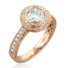 Sculpted Halo Rose Gold Engagement Ring from Yael Designs - Engagement ring from the Novelique collection features a halo that surrounds the center stone (fits a 1.0 ct.), with a sculpted, edged design that extends down the band, set throughout with round diamonds. MSRP: $2,653