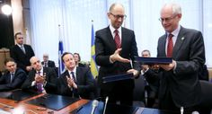 krainian Prime Minister Arseniy Yatsenyuk, second right, and European Council President Herman Van Rompuy, right, hand each other their books during a signing ceremony at an EU summit in Brussels on Friday, March 21, 2014. Ukraine's prime minister has pulled his nation closer into Europe's orbit, signing a political association agreement with the EU at a summit of the bloc's leaders.