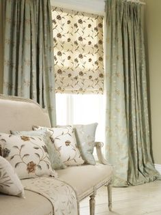 Prestigious Textiles - Bloom Fabric Collection - Grand blue curtains with a classic floral decoration and white blinds with a grey floral grid, behind an antique couch with cushions