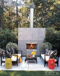 Influenced by the indoor-outdoor lifestyle of Southern California and the clean-lined architecture of Tadao Ando, decorator Eric Hughes created a minimalist terrace for entertaining at his house in Wainscott, New York. The furniture has a modern Asian look, amplified by a pair of colorful ceramic stools from Mecox Gardens; the fireplace wall is poured concrete.
