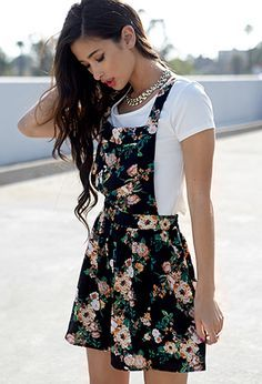 Black Floral Skirt Style Dungaree Paired With White Tee-Shirt And A Neck-Piece.