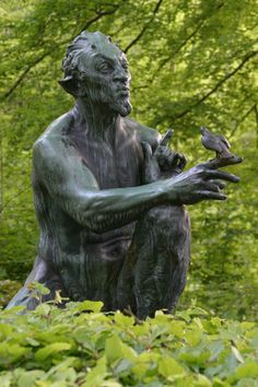 A statue of Pan whistling to a small bird, located in the Forest of Marselisborg, in Southern Aarhus, Denmark.