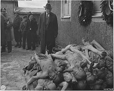 German civilians are compelled by Allied soldiers to view the carnage at Buchenwald.