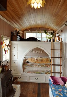 """Above the """"canopied"""" bed, there is a sitting area that is structured under a wood paneled ceiling."""