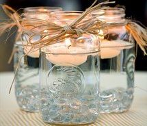 jars, your choice of colored, or not, pebbles on bottom, floating candle, tied with ribbon or whatever