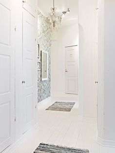 White wooden floors and printed wallpaper with matching rugs. How RIDICULOUSLY perfect is this entrance?
