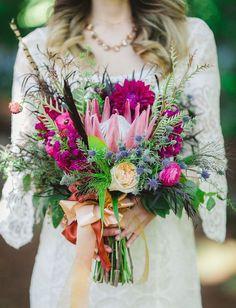 Csodaszép, különleges, élénk színű menyasszonyi csokor proteával és madártollal. Leginkább nyári esküvőhöz illik, de olyan egyedi és vidám, hogy egész évben szívesen találkoznánk vele.