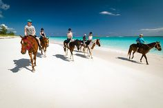 Riding horseback on the pink sand beaches of Eleuthera, Bahamas near Pineapple Fields Resort.