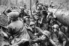American infantrymen crowd into a mud-filled bomb crater and look up at tall jungle trees seeking out Viet Cong snipers firing at them during a battle in Phuoc Vinh, north-Northeast of Saigon in Vietnam's War Zone D on June 15, 1967