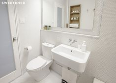 Brooklyn bathroom renovation with wall-mounted sink and dual-flush Kohler toilet skirted to conceal piping.