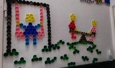 The wall full of plastic bottle caps: kids playing