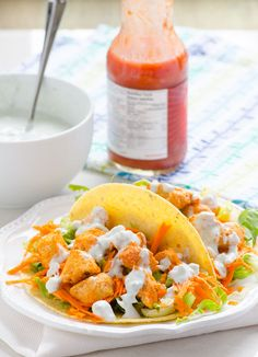 Clean Eating Buffalo Chicken Tacos -- Chicken coated in cayenne hot sauce and drizzled with homemade blue cheese sauce, wrapped in organic corn tortilla and topped with shredded lettuce and carrots. To die for. #glutenfree